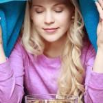 Frau mit Erkältung über einem Kamillendampfbad