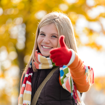 Smiling autumn teenager girl thumbs up forest