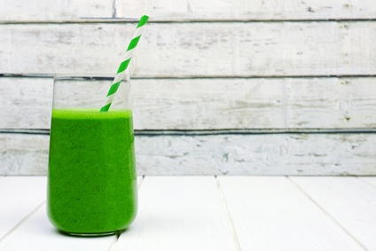 Green kale smoothie in a glass with straw on a rustic white wood background