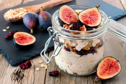 Jar of overnight autumn oats with red figs, cranberries and walnuts against a rustic wood background