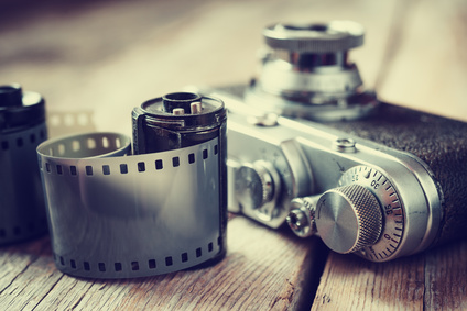 Old photo film rolls, cassette and retro camera, selective focus. Vintage stylized.
