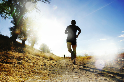 Silhouette of young sport man running on countryside in cross country competition at summer sunset with harsh high contrast sunlight effect and flare in healthy lifestyle concept