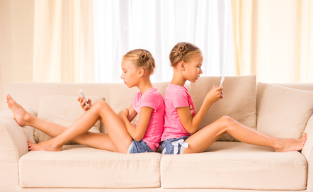 Young twins sisters are using smartphone sitting on the couch.