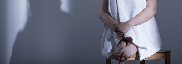 Panorama of scared rape victim sitting curled on chair